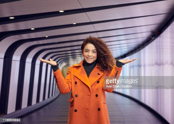 portrait of young woman gesturing while standing in corridor - three quarter length stock pictures, royalty-free photos & images