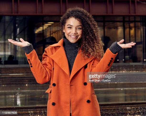portrait of young woman gesturing while standing outdoors - three quarter length stock pictures, royalty-free photos & images