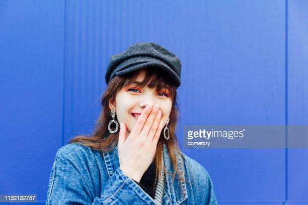 portrait of young woman  hands covering mouth smiling - hands covering mouth stock pictures, royalty-free photos & images