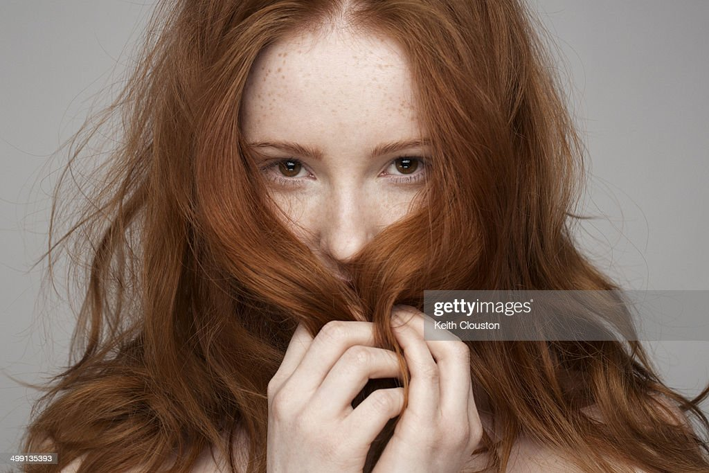 Portrait of young woman, hands in hair : Stock Photo