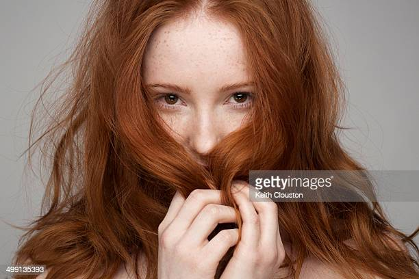 portrait of young woman, hands in hair - redhead stock pictures, royalty-free photos & images