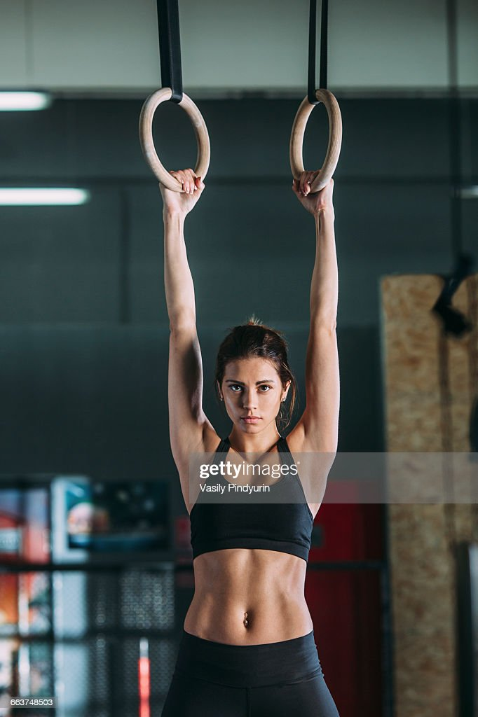 Portrait of young woman hanging from gymnastic rings : Stock Photo