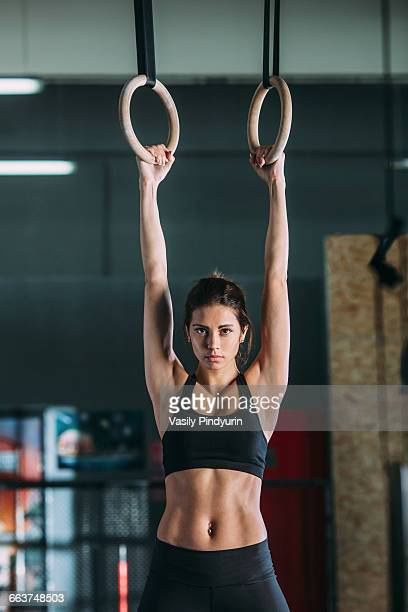 Portrait of young woman hanging from gymnastic rings
