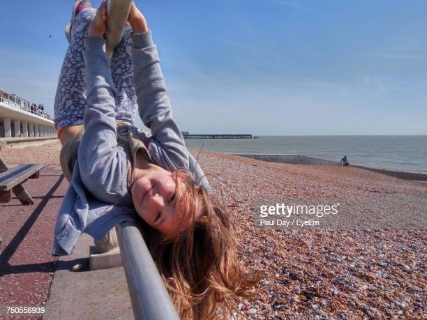 portrait of young woman hanging to railing by beach against sky - hastings stock photos and pictures
