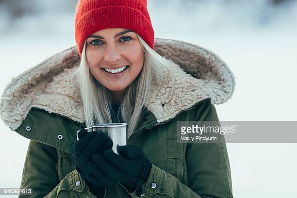 Portrait of young woman having coffee during winter