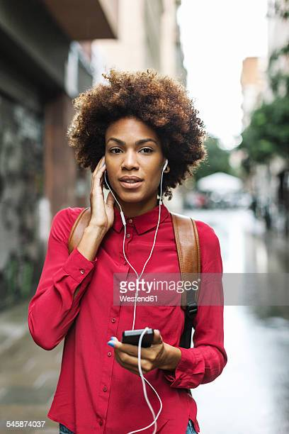 Portrait of young woman hearing music with earphones