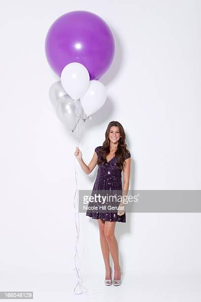 portrait of young woman holding balloons at party - una sola mujer joven fotografías e imágenes de stock