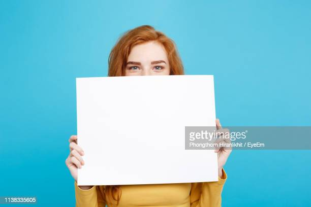 portrait of young woman holding blank placard while standing against blue background - halten stock-fotos und bilder