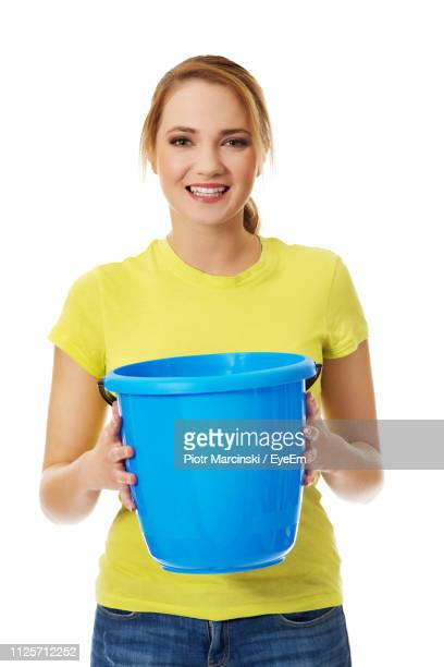 portrait of young woman holding blue bucket against white background - bucket stock pictures, royalty-free photos & images