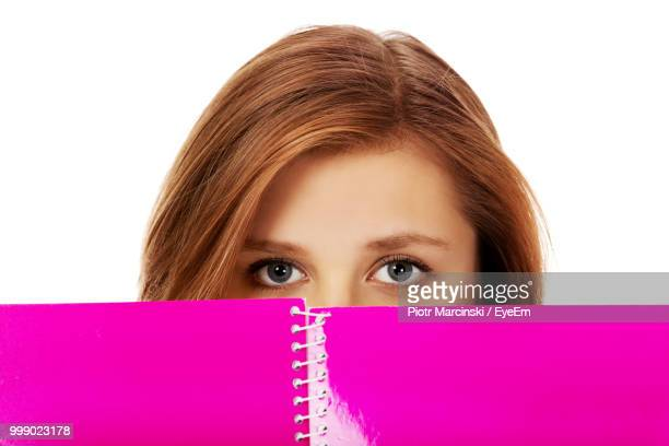 Portrait Of Young Woman Holding Book Against White Background