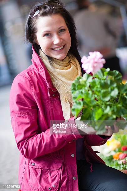 Portrait of young woman holding bunch of flowers
