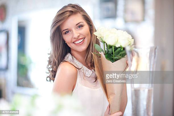Portrait of young woman holding bunch of roses