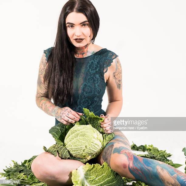 Portrait Of Young Woman Holding Cabbage While Sitting On White Background