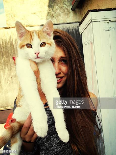 Portrait of young woman holding cat outdoors