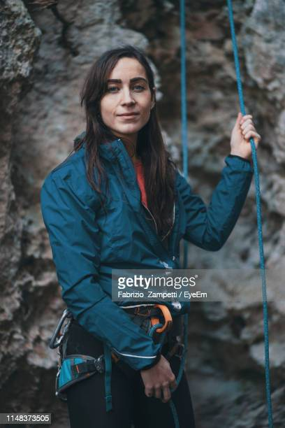 Portrait Of Young Woman Holding Climbing Rope While Standing By Mountain