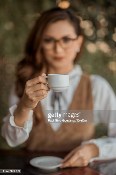 portrait of young woman holding coffee cup while sitting in cafe - negros oriental stock pictures, royalty-free photos & images
