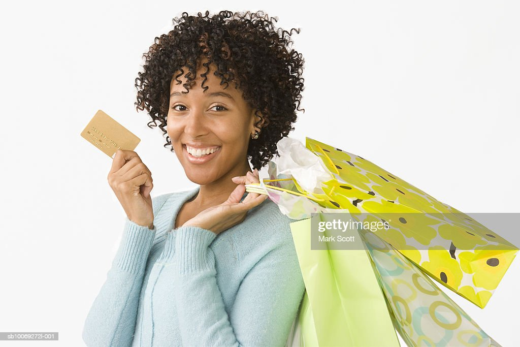 Portrait of young woman holding credit card and shopping bags : Stockfoto