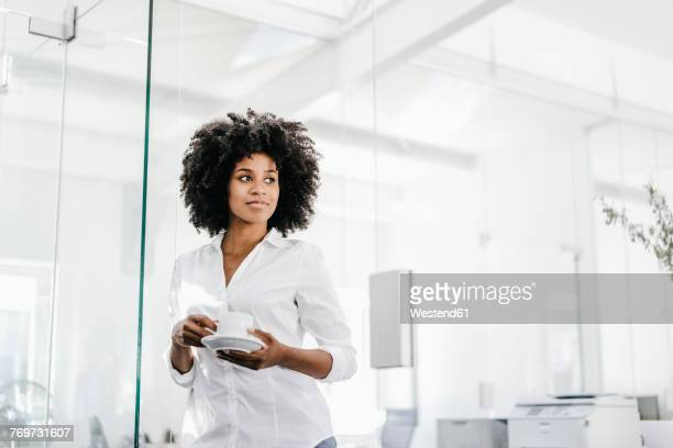 portrait of young woman holding cup of coffee in office - blouse stock pictures, royalty-free photos & images