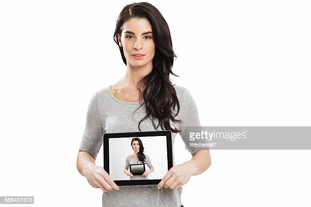 Portrait of young woman holding digital tablet with selfie