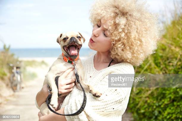 Portrait of young woman holding dog on her arms