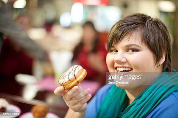 portrait of young woman holding doughnut - fat people eating donuts stock pictures, royalty-free photos & images