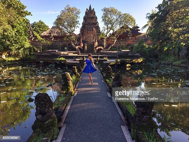 Portrait Of Young Woman Holding Dress On Pathway At Ubud Palace