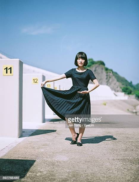 portrait of young woman holding dress while standing on street during sunny day - fringe dress stock photos and pictures