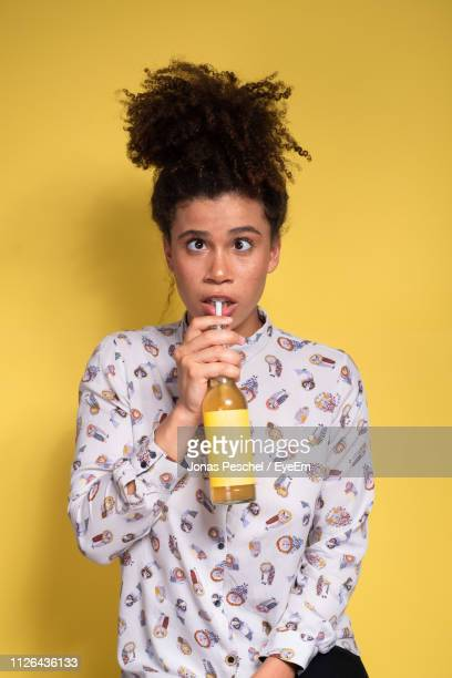 portrait of young woman holding drink against yellow background - cross eyed stock pictures, royalty-free photos & images