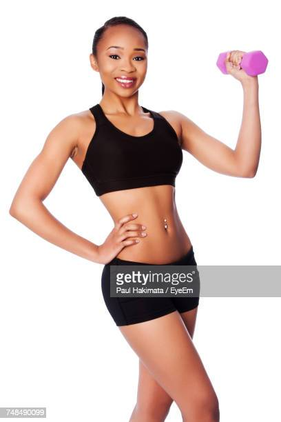 portrait of young woman holding dumbbell against white background - black shorts stock pictures, royalty-free photos & images