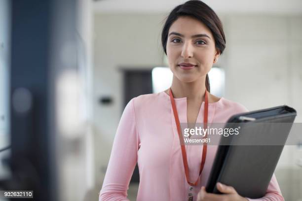 portrait of young woman holding folder on the corridor in office - one young woman only stock pictures, royalty-free photos & images