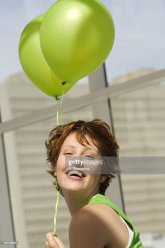 Portrait of young woman holding green balloons : Stock Photo