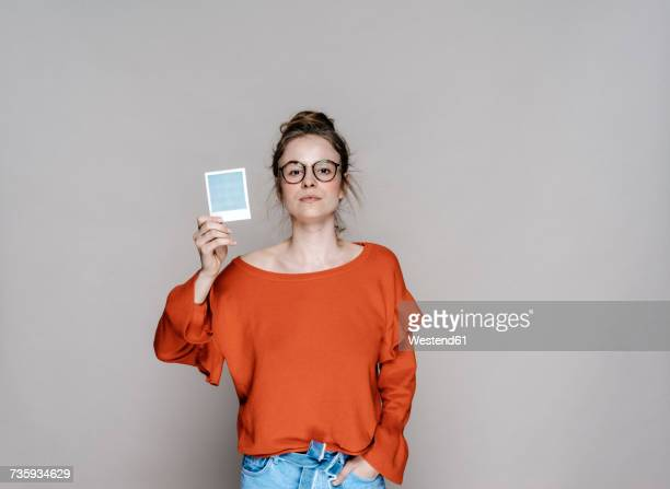 portrait of young woman holding instant photo - portrait photos stock photos and pictures