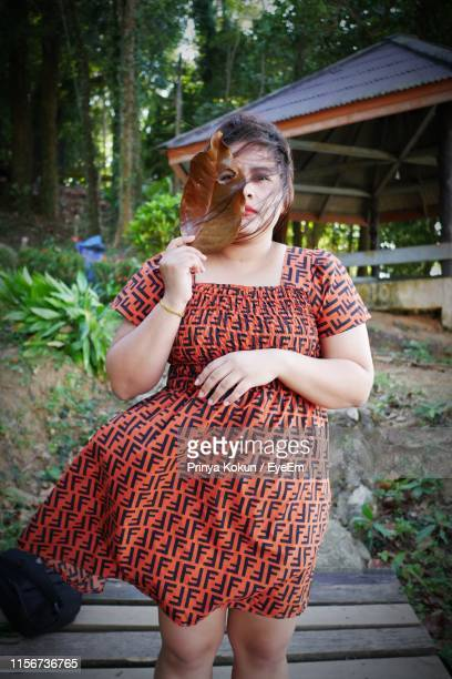 portrait of young woman holding leaf while standing in forest - chubby asian woman stock pictures, royalty-free photos & images