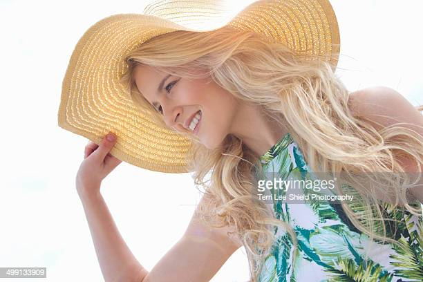 portrait of young woman holding onto sunhat - blyth northumberland stock pictures, royalty-free photos & images