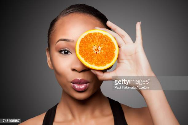 Portrait Of Young Woman Holding Orange Slice In Front Of Eye Against Gray Background