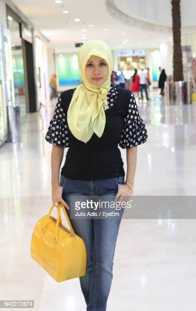 portrait of young woman holding purse at shopping mall - julis stock pictures, royalty-free photos & images