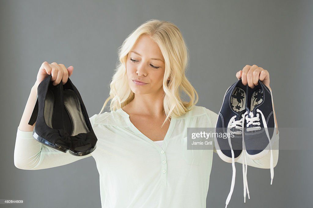 Portrait of young woman holding shoes, Jersey City, New Jersey, USA : Stock Photo