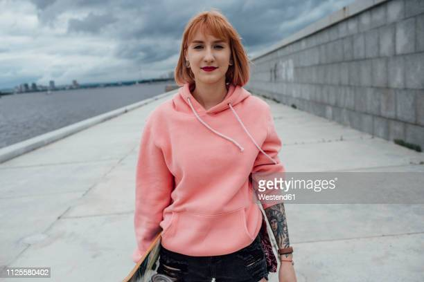 portrait of young woman holding skateboard at the riverside - hooded top stock pictures, royalty-free photos & images