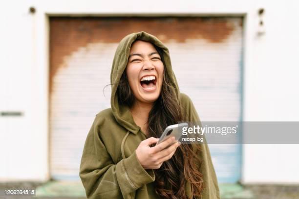 portret van jonge vrouw die slimme telefoon houdt en het lachen - lachen stockfoto's en -beelden