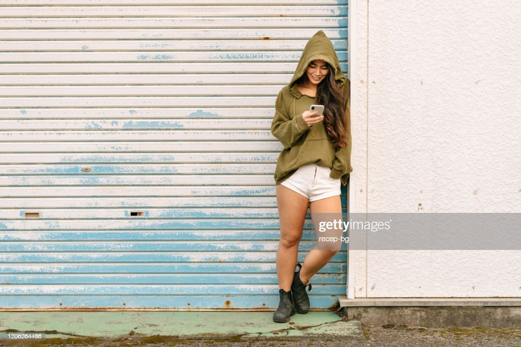 Portrait of young woman holding smart phone : Stock Photo