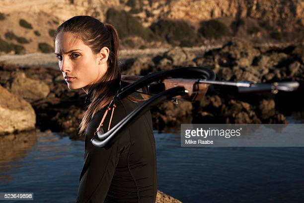 Portrait of young woman holding speargun, Palos Verdes Peninsula, Los Angeles County, California, USA