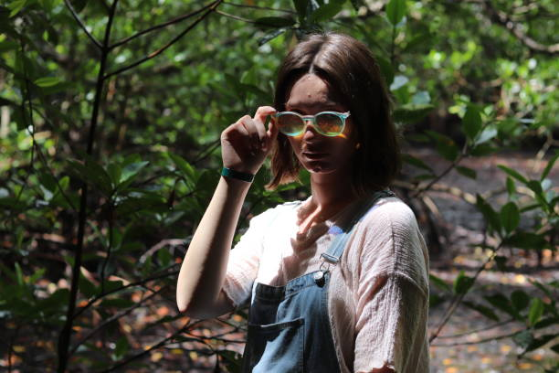Portrait Of Young Woman Holding Sunglasses Against Trees