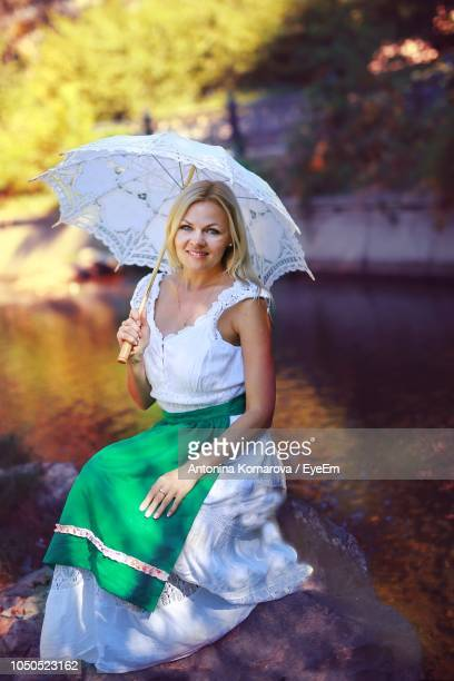 Portrait Of Young Woman Holding Umbrella While Sitting On Rock
