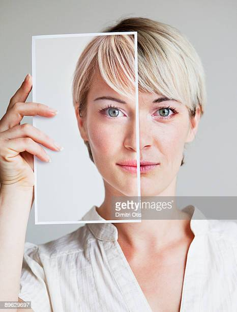 portrait of young woman holding up a her picture - obscured face stock pictures, royalty-free photos & images