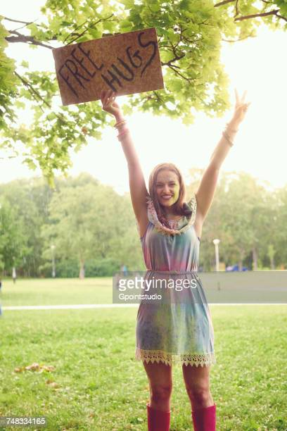 Portrait of young woman holding up free hug sign at festival