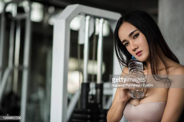 Portrait Of Young Woman Holding Water Bottle While Standing In Gym