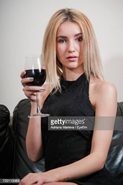 portrait of young woman holding wineglass on sofa at home - ノースリーブ ストックフォトと画像