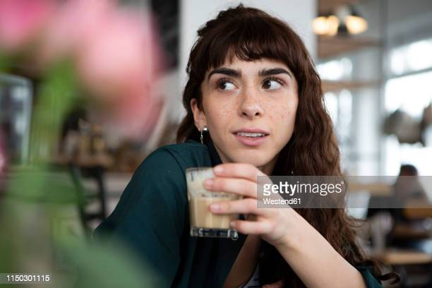 portrait of young woman in a cafe looking around - braune augen stock-fotos und bilder