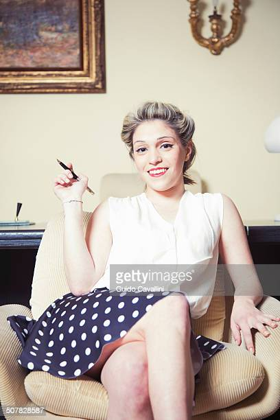 Portrait of young woman in armchair wearing vintage clothes