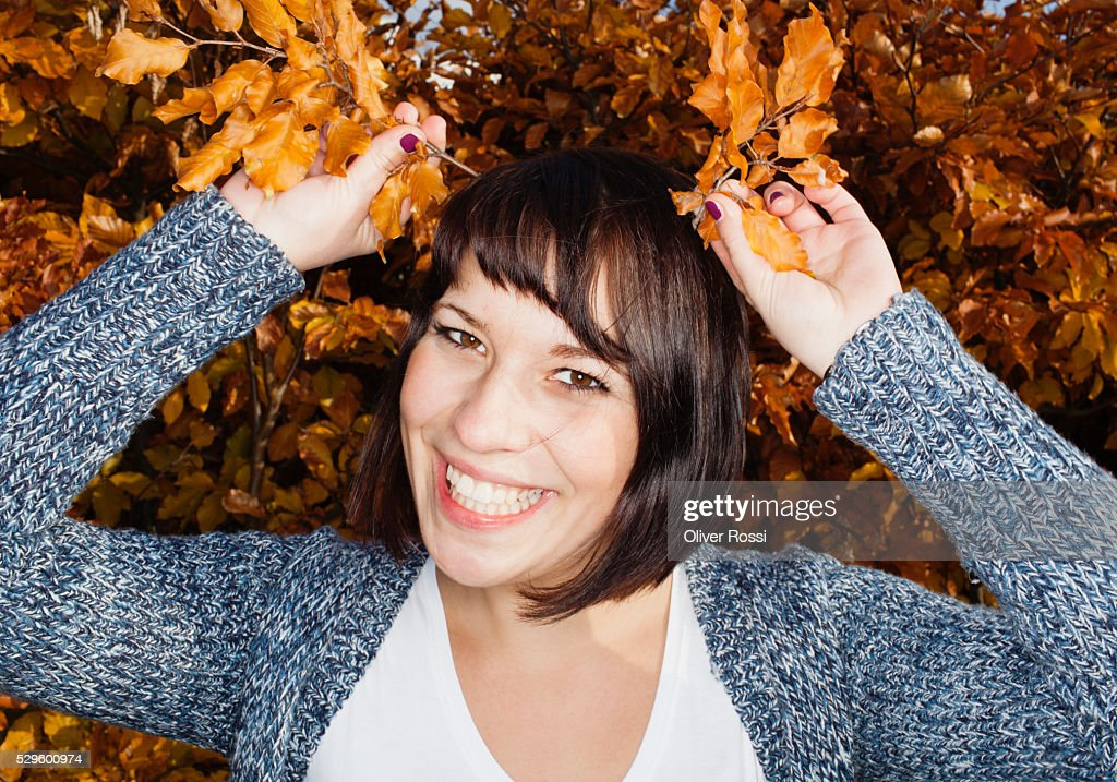 Portrait of young woman in autumn foliage : Stock Photo